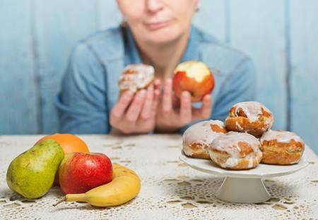 Woman choosing between fruit and sweets