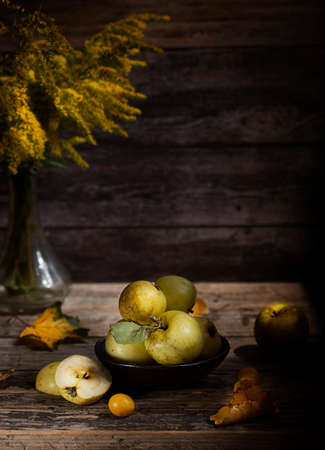 Wild, yellow apple on wooden background