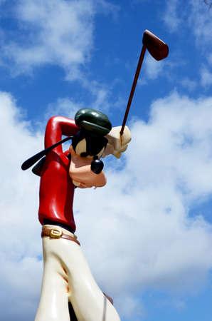 Monchique, Faro - Portugal, Circa, March 2013. Studio image of Goofy figure swinging a golf club with a blue sky background. Goofy was produced by Walt Disney. Redakční