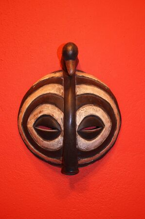 African mask on a red isolated background.