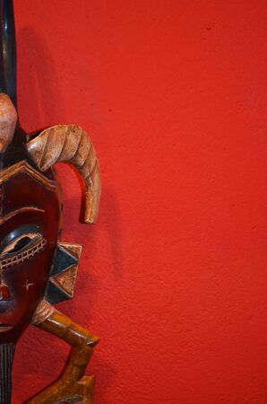 Half of an African mask on a red isolated background. allowing room for text.