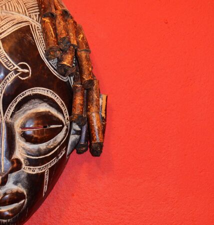 African half mask on a red isolated background. Allowing space for text. Stock fotó