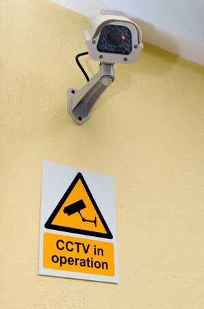Security camera mounted on a wall of a house with a CCTV in operation sign below.