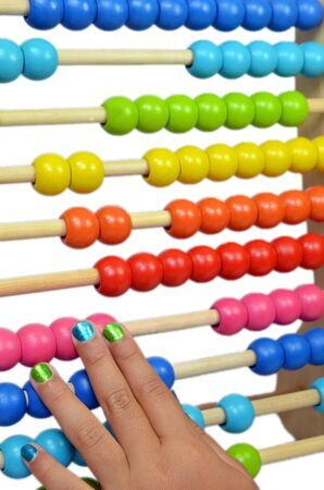 Child playing with a colorful Abacus with a isolated white
