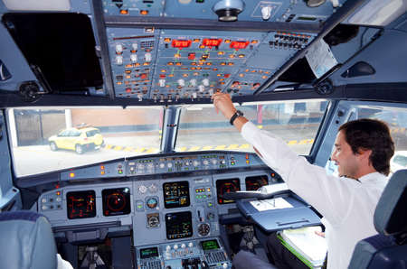 Portugal, Algarve, Faro. Circa 10th July 2013. Picture of a tap airline commercial airplane cockpit with Pilot reaching out for controls. Picture taken taken when plane landed at destination at Faro. Éditoriale