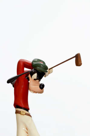 Monchique, Faro - Portugal, Circa, March 2013. Studio image of Goofy figure swinging a golf club with a white isolated background. Goofy was produced by Walt Disney.