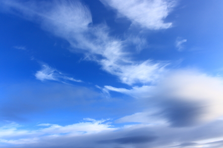 Landscape clouds are amazing in colors and shapes against the background of a high bright blue sky. Gray cloud in the shape of a ball in the foreground. Non-standard celestial landscape Stock Photo