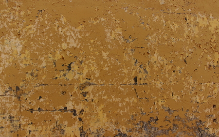 Rough dirty concrete wall with cracked paint of a nasty mustard color background. Old dirty nasty plaster on the wall surface. Stock Photo