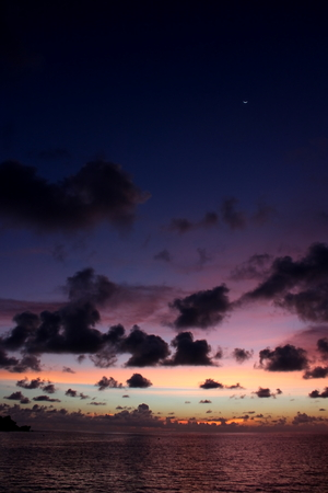 Amazing twilight sky with beautiful clouds on a paradise tropical island. There is a silver crescent moon in the sky 版權商用圖片