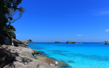 A paradise tropical landscape with idyllic bright azure clear water and the perfect blue sky. In the background in the transparent sea are high-speed boats. Classical representation of beach rest. 스톡 콘텐츠