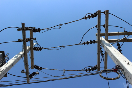 Electrical insulators and wires on concrete pillars on clear blue sky background in the Thailand