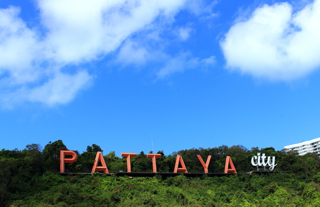 Red and white letters Pattaya city on the hill Pratumnak, Pattaya, Thailand against a background of tropical trees and blue sky on a sunny day. 版權商用圖片