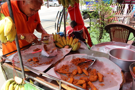 Pattaya City, Thailand - Mart 21, 2018: an elderly Thai man puts fried bananas and papaya in a plastic bag from a street counter. Adult man sells fried in battered bananas