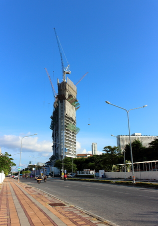 Pattaya City, Thailand - Mart 18, 2018: City landscape with a high-rise building of a new hotel under construction. Tower cranes are located on the roof of the building under construction