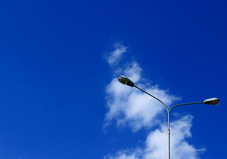 Lighting lamp, street lights, lamppost against the vast blue sky with cloud - abstract minimalism background wiht copy space. Lanterns on outdoor Stock Photo