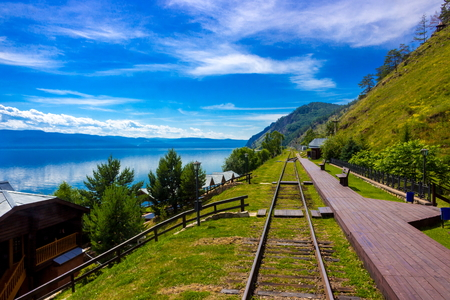 Majestic summer landscape on Lake Baikal for travel background with wooden deserted platform station Circum-Baikal railway in a bright summer sunny day. 免版税图像