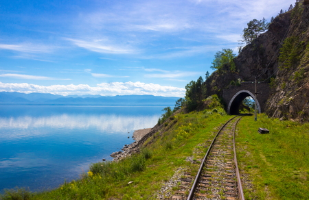 Old stone arch tunnel in mountain the rock on the Circum-Baikal railway. Idyllic background of a summer landscape with mountains and lake Baikal for transfer of an aura of wanderlust
