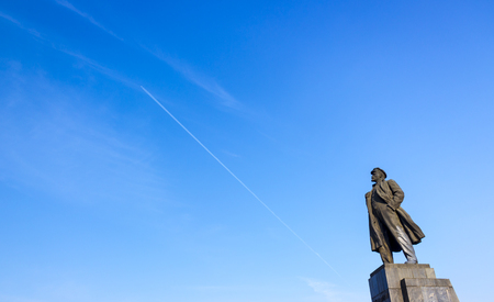 Krasnoyarsk, Russia - June 27, 2018: a monument to Vladimir Lenin in Krasnoyarsk against the backdrop of a bright blue sky with a flying airplane. 1970 installation of the monument. The author of the monument is sculptor Veniamin Pinchuk Standard-Bild - 110653748