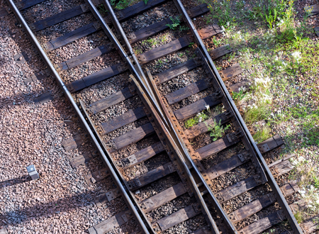 Switching arrows and two old railroad tracks with wooden sleepers as a concept background. Top view Stock Photo