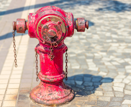 Typical old red fire hydrant with rusty chains on the sidewalk in Hong Kong city on a sunny day