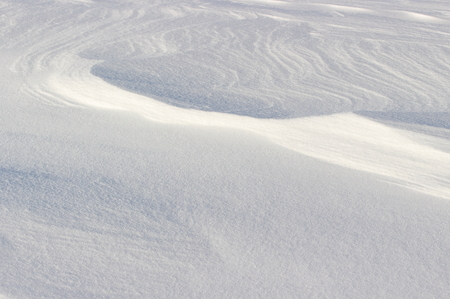 Beautiful natural background of white snow drifts and dunes. Strong wind makes fancy patterns and textures on the hard surface of the snow field. Stock Photo