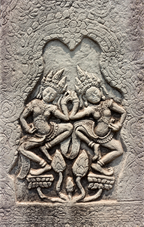 Dancing Apsaras of detail religious stone carving decorating on ancient wall Angkor Wat Temple at Siem Reap, Cambodia. Khmer architecture in the modern world.