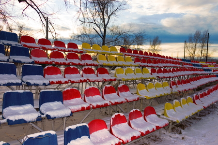 Sports stadium bleachers in winter, colorful chairs of the fans - empty seats on grandstands covered by snow. Concept of winter sports and game outdoors. Snow covered tribune on dusk background