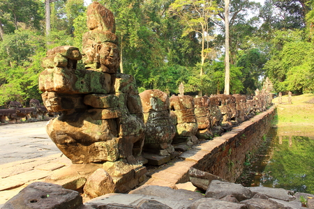 Old stone bridge decorated with ruined statues to the Preah Khan Temple at Angkor Wat complex in Siem Reap, Cambodia.