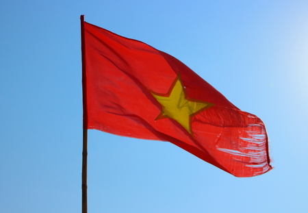 Old tattered national flag of the Vietnam against a clear blue sky