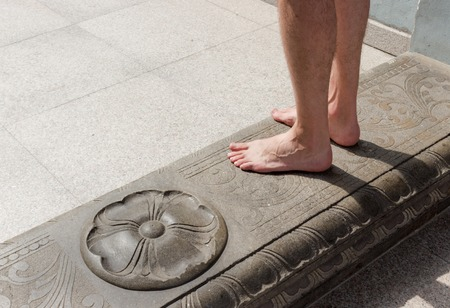 The bare feet of a male traveler on the doorstep of a Sri Maha Mariamman Temple adorned with an ancient ornament at Kuala Lumpur, Malaysia Stockfoto