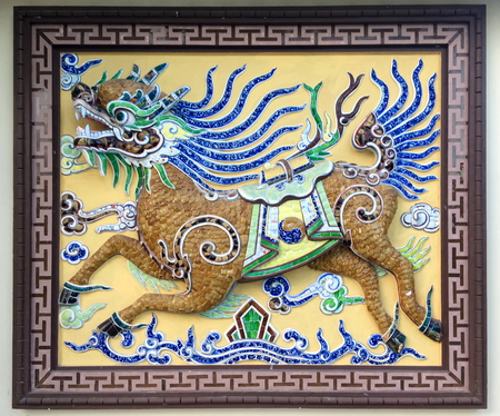 Chinese traditional old ceramic mural painting of Qilin. The Kirin of Chinese fables, with the body of a horse and the head of a dragon on wall of Chinese temple in Nha Trang, Vietnam