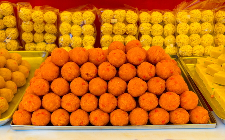 Indian traditional diwali sweets called Motichoor Ladoo on the counter of a street vendor on a sunny hot day near Batu Caves, Kuala Lumpur, Malaysia Reklamní fotografie
