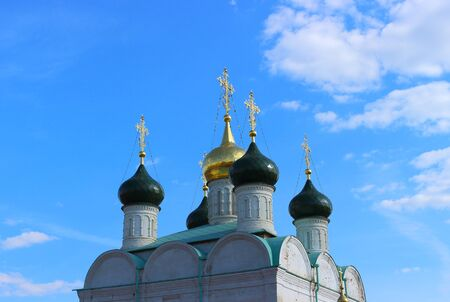 Shined golden crosses on the green and golden orthodox domes of St. Nicholas Cathedral on blue sky background. Background for religious greeting card with copy space