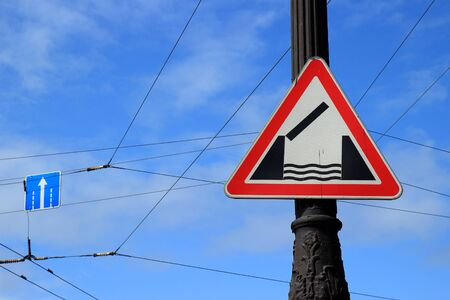 Warning road sign 'Drawbridge' on pillar against the background of the blue sky. Installed in front of a swing bridge or ferry