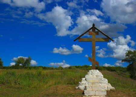 Una croce lungo il cammino su una pietra bianca sullo sfondo di un campo estivo e un campo blu.
