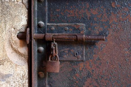 Closed rusty vintage metal latch with an old padlock on a weathered metal door. Prison concept background. Selective focus Stock Photo