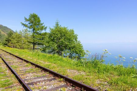 Rails of the Trans-Siberian Railway on the shore of Baikal Lake going into the distance. Summer on Circum-Baikal Railroad. 写真素材