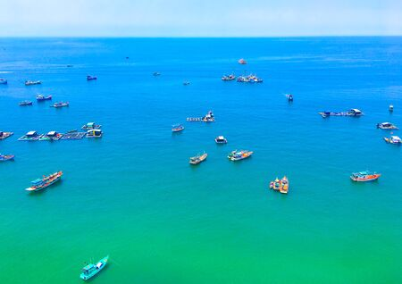 Traditional colorful fishing boats in the azure sea in Phu Quoc island, Vietnam. View from of a cable car.