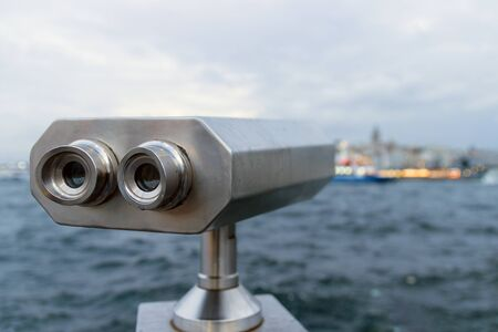 Tourist telescope against blurred sea background. Binoculars for sightseeing. Selective focus