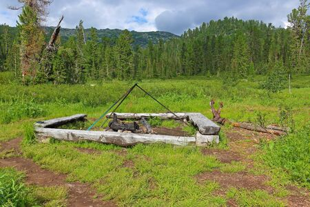 Place for the bonfire in the camping. Equipped campfire site. Sunny summer landscape in taiga forest. Nature park Ergaki, Russia, Siberia. Eastern Sayan mountains.