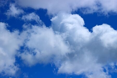 Awe background with bright blue sky and white fluffy clouds