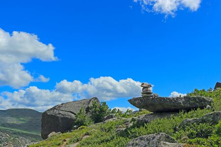 Cairn in mountains against blue sky. Stone pyramid on the mountain trail for the route and protect of the traveler. Zen balanced stones. Nature park Ergaki, Russia, Siberia.