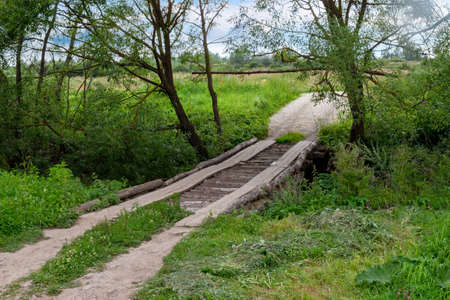 Homemade log bridge over a ditch on a rural road. Summer landscape in the Russian village. Wooden flooring for transportation