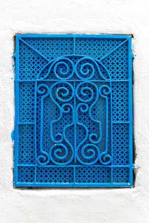 Tunisian blue window with decorative grid in white wall. Typical house in the medina of Hammamet town, Tunis. House details in North Africa 版權商用圖片