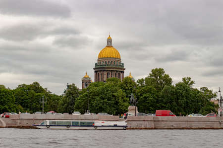 Saint Petersburg, Russia - 11 August, 2020: View on gold dome of St. Isaac's Cathedral and monument of the Bronze Horseman from the Neva River on a cloudy summer day