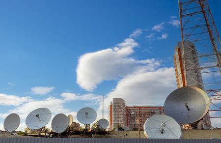 Many parabolic antennas against sky in city. Satellite communications dish. Home TV antenna.