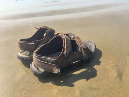 Grunge mens sandals left on wet sand by the sea for summer background