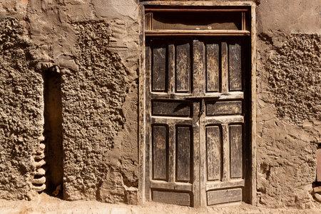 Ancient wooden door in stone wall at medina of Marrakesh, Morocco