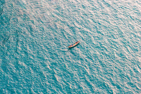 Boat with fisherman on rippled blue sea water surface. Aerial view