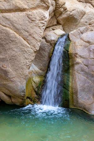 Small waterfall among the rocks in oasis of Chebika near Nefta at Sahara desert, Tunisia. Motion blur water Standard-Bild